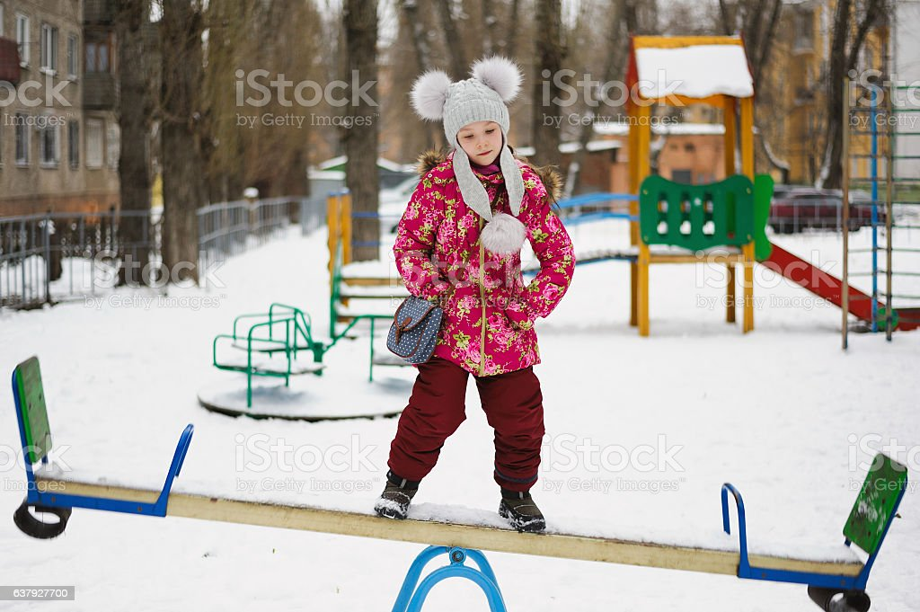 balancing girl stand on teeter-totter stock photo