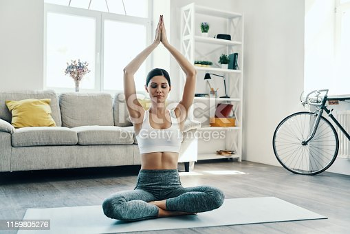 Beautiful young woman in sports clothing practicing yoga while spending time at home