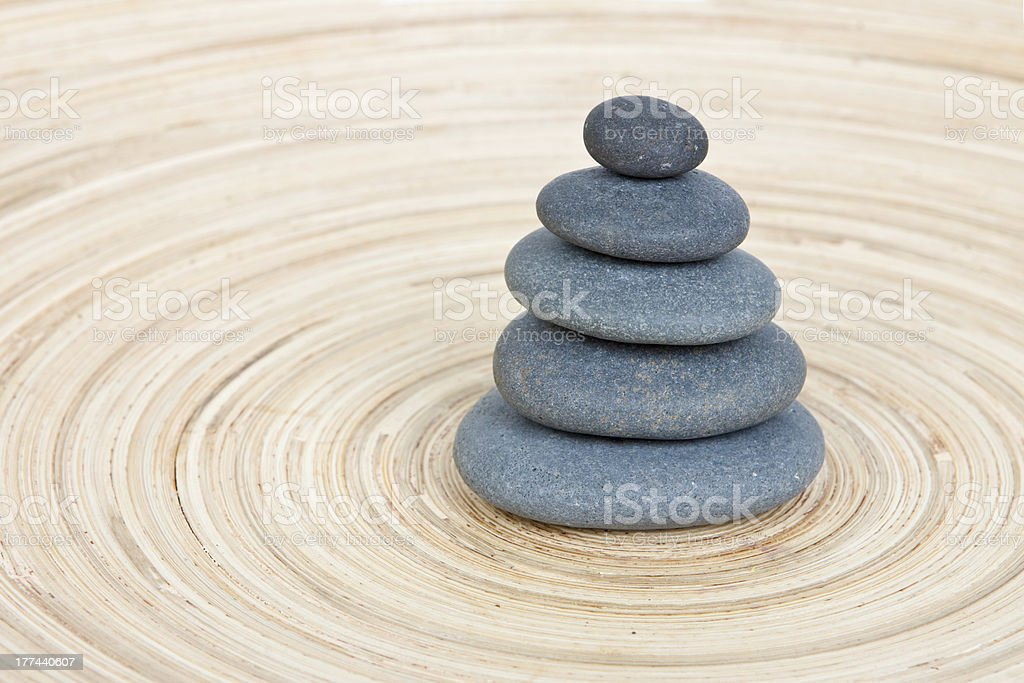 Balancing of pebbles on wooden background royalty-free stock photo