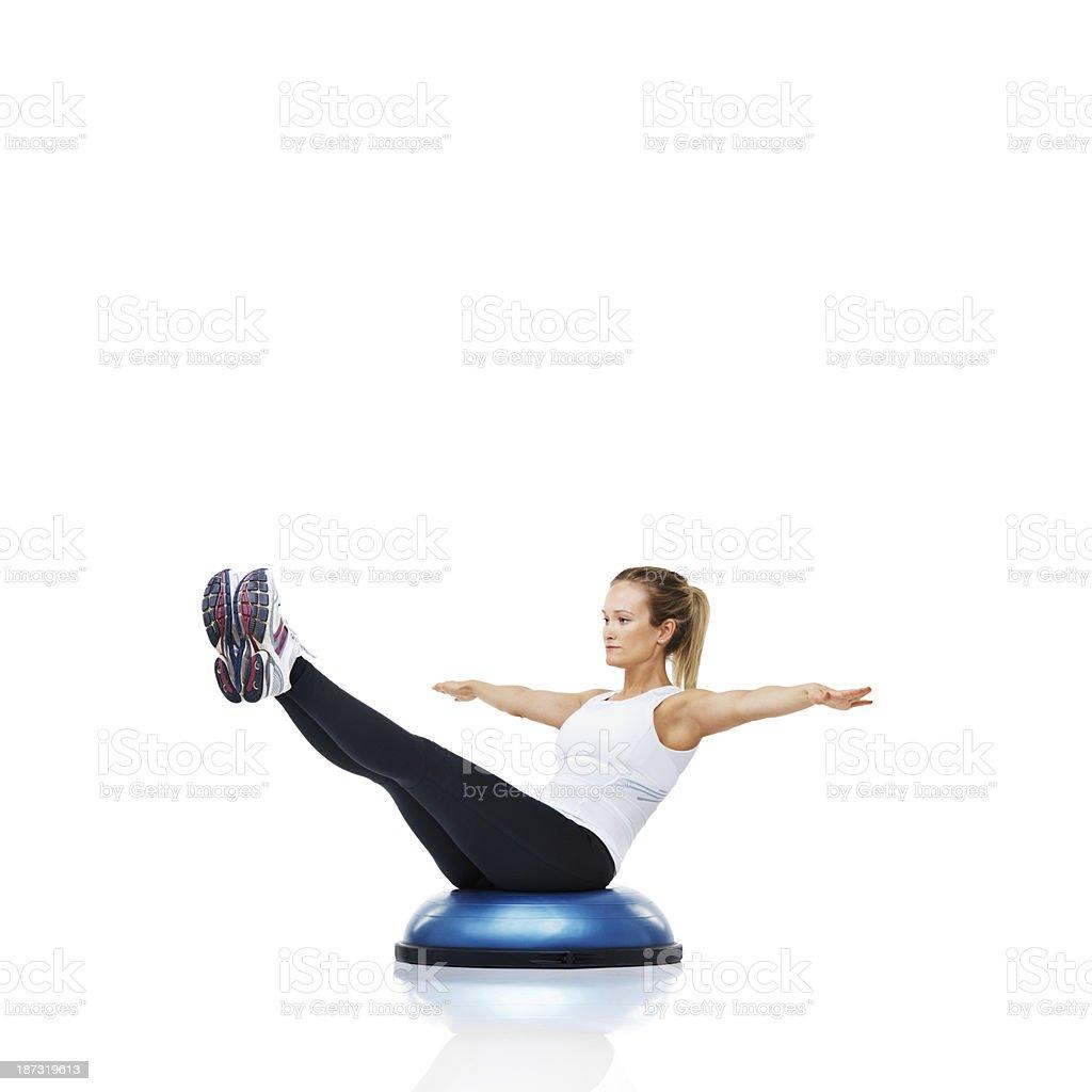 Balancing on a bosu-ball to increase her core strength stock photo