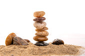 Balancing pebble stones on sand