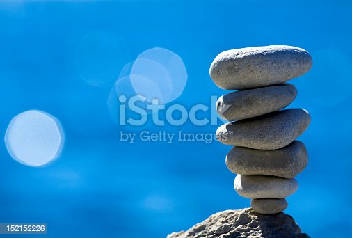 Close-up of pebbles stack over blue sea