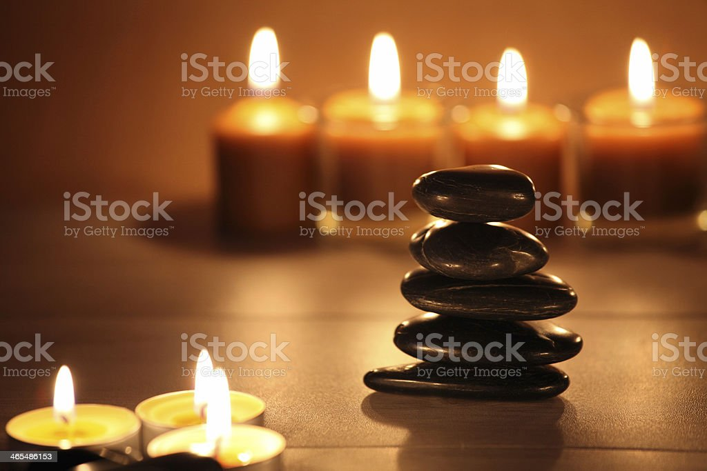 balancing zen stones and pebbles with candles on wooden table stock