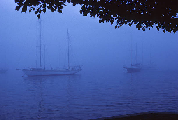 Balboa Bay, foggy morning, 1980 A few boats are barely visible through the fog over Balboa Bay in Newport Beach, California. hearkencreative stock pictures, royalty-free photos & images