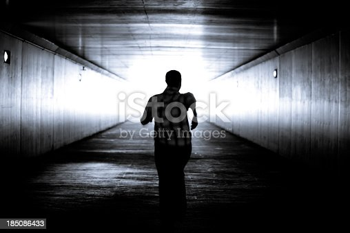 Black and white conceptual image.Man is running out of the tunnel into the light.  Motion blur. He is determined to get out of darkness into the light. There is hope and determination.