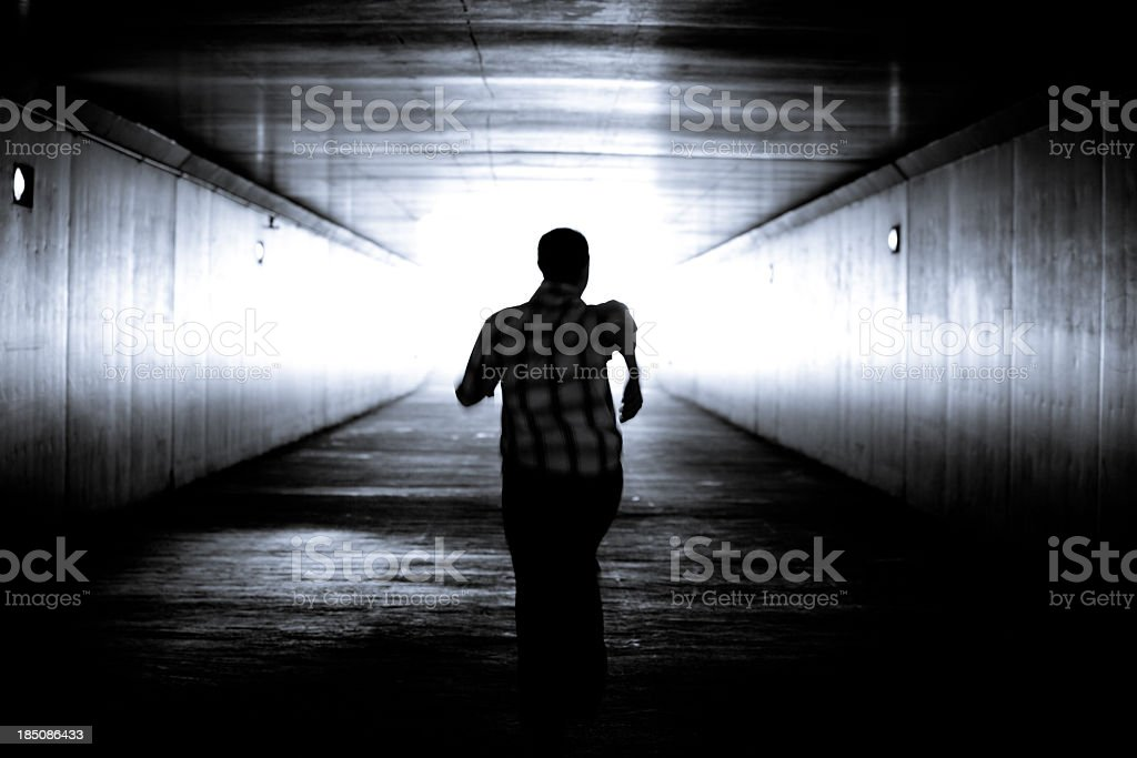 Balck and white image of man's silhouette running stock photo