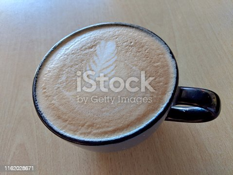 Balck cup of Cappuccino on saucer with a leaf pattern in foam on table.