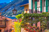 Balconies flowerbeds and street light lamp above Lake Como, old town – Bellagio, Italy