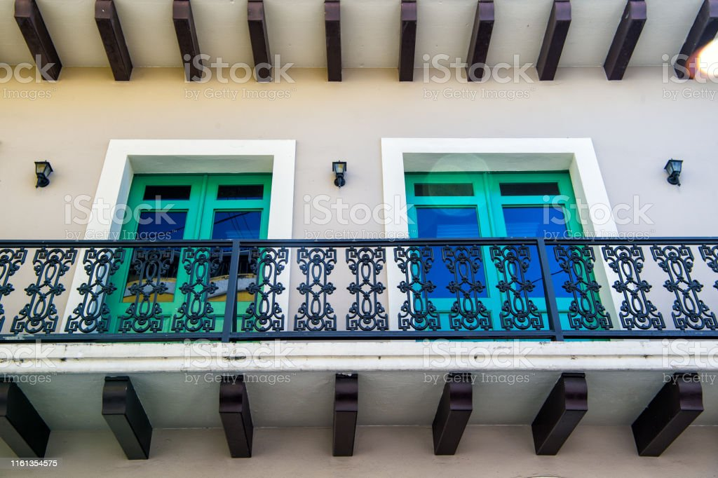 Balcony with metal railing and two windows with green frames on...