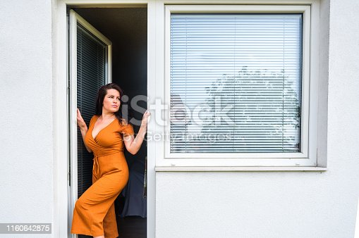 young woman opens pvc balcony door with jalousie