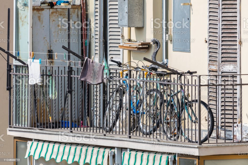Balcony of a building in the suburbs, with a rusty wardrobe, two bicycles and a plastic snake (Turin, Italy) stock photo