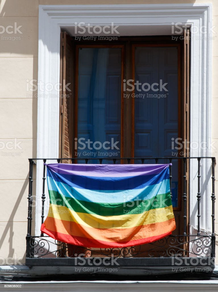 Balcony of a house decorated with the rainbow flag of gay pride stock photo