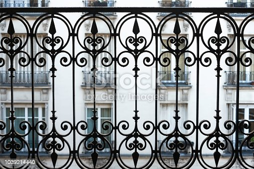 Close-up shot of balcony with wrought iron railing in parisian home.