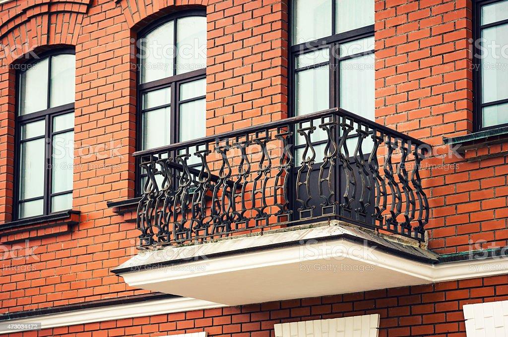 Balcón con hierro forjado alrededor de un edificio de ladrillos - foto de stock