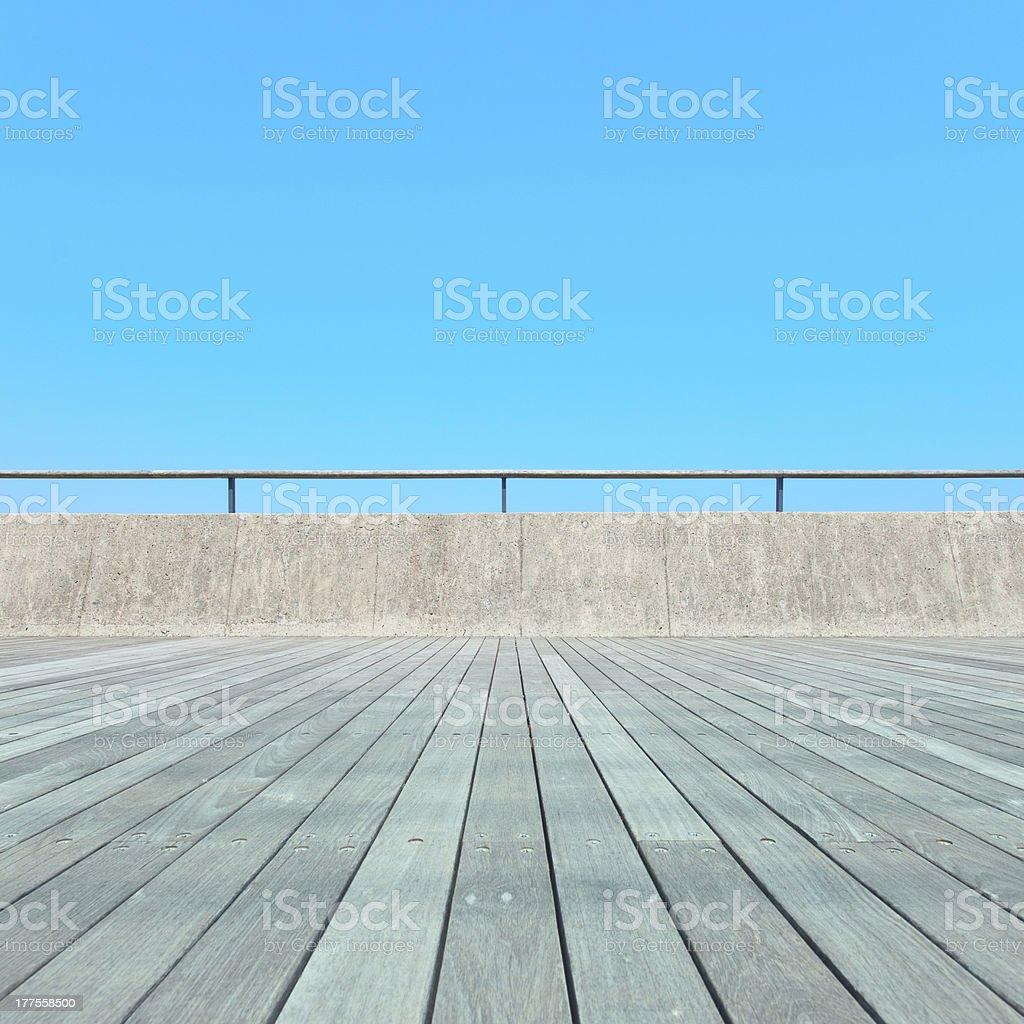 Balcony, Wood plank floor, concrete fence, blue sky. Bottom view royalty-free stock photo