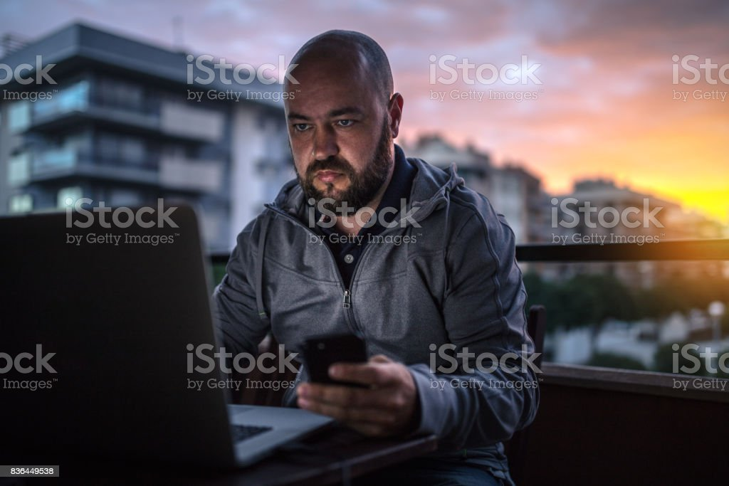 Bald and bearded men uses laptop and smartphone at sunset stock photo