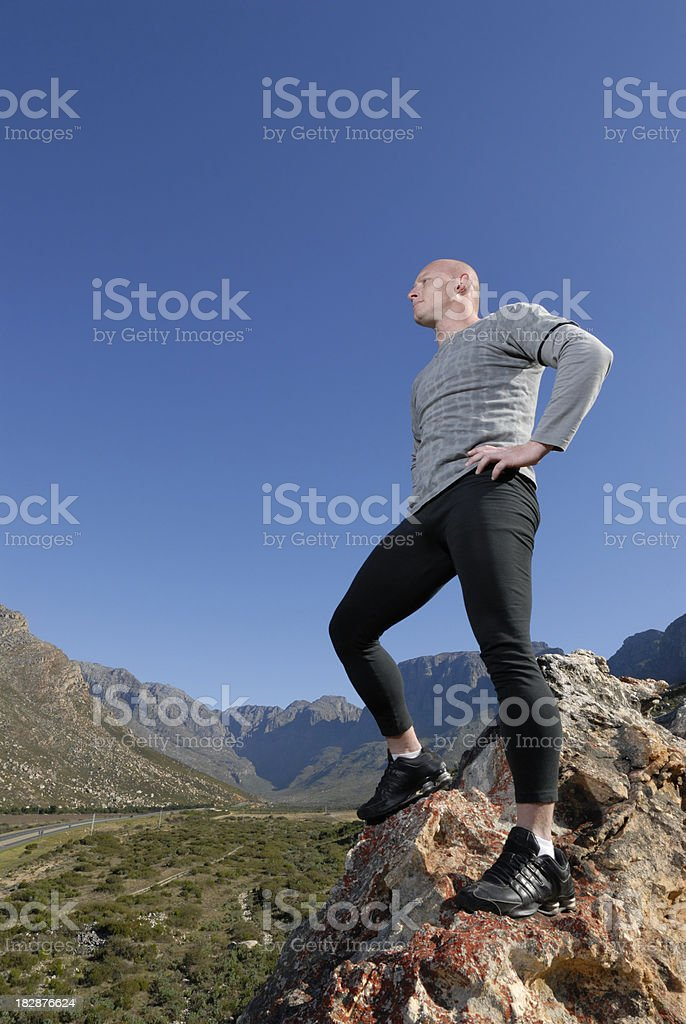 Bald athlete on rock confident stock photo