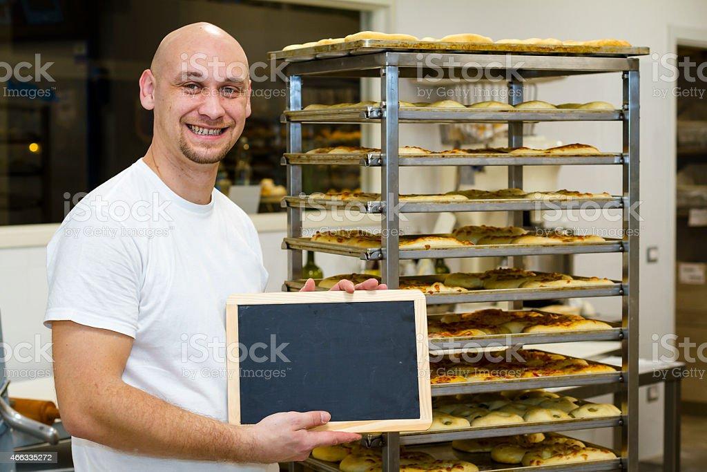 Bald Baker holding blackboard near a rack with baking tins stock photo
