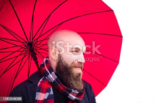 bald bearded man wearing a scarf and warm winter clothes holding a red umbrella as a background.smiling young adult on a white scenario in a studio shooting.concept about joy,happiness and natural beauty