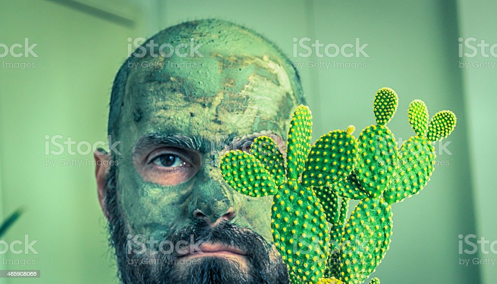 Bald bearded man with facial clay mask and his cactus. stock photo