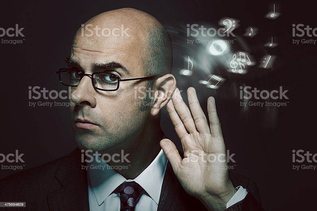 Bald businessman listening to music stock photo