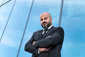 istock bald businessman with arms crossed standing at office-building 636631846