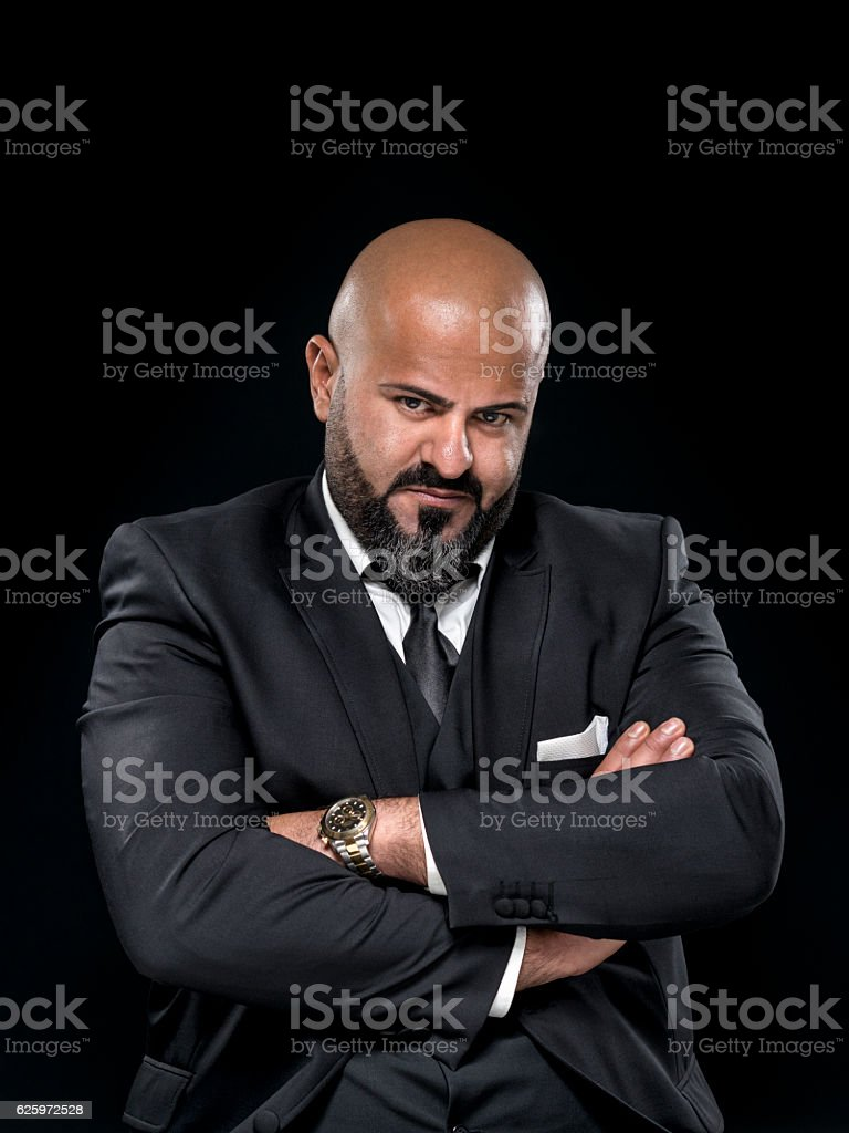 bald businessman with black beard and arms crossed stock photo