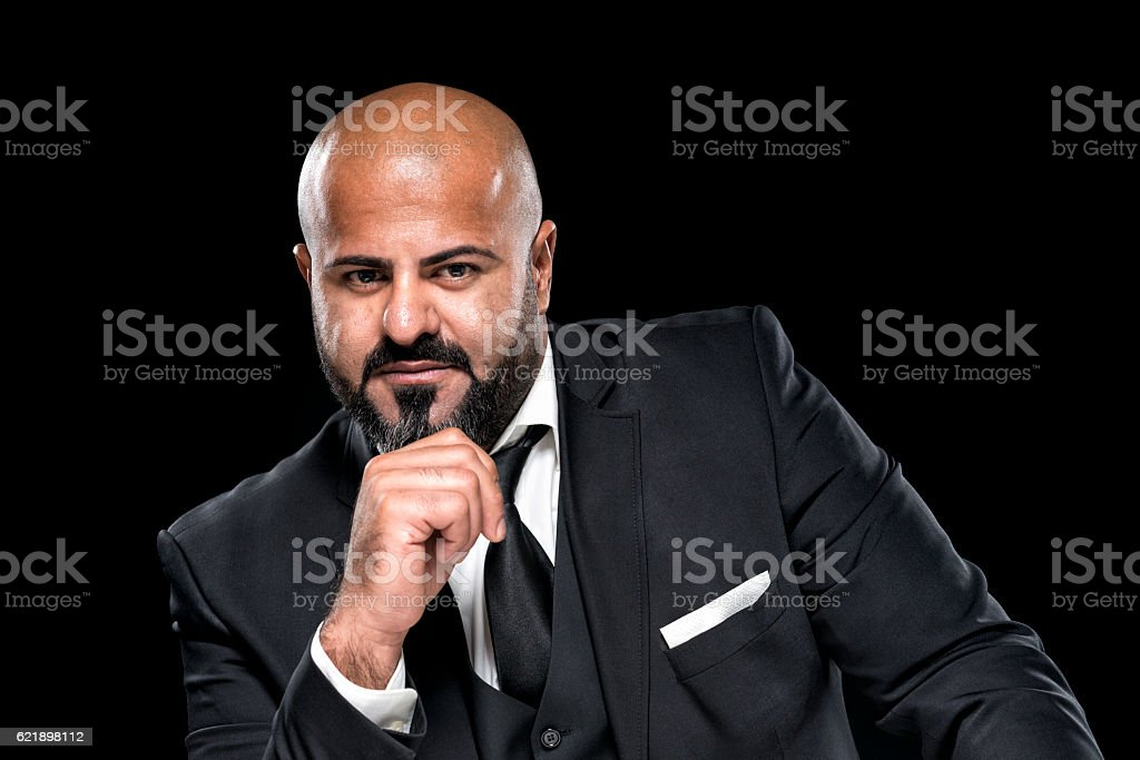 bald businessman with black beard looking serious stock photo