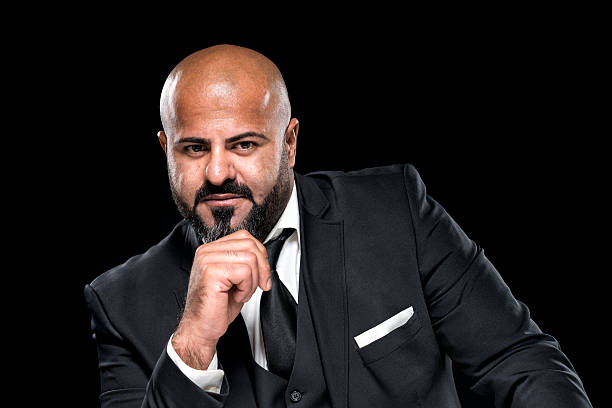 bald businessman with black beard looking serious stock photo
