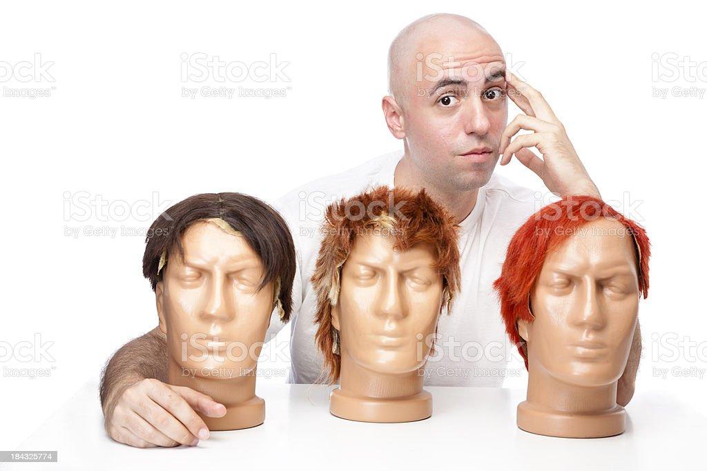 Bald guy choosing his new wig royalty-free stock photo