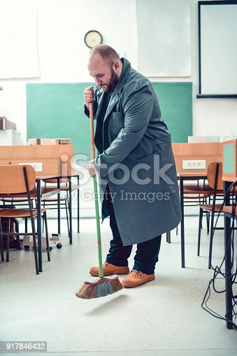 istock Bald Janitor Cleaning in Engineers Classroom 917846432