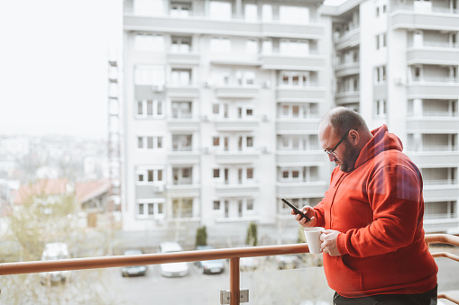 Bald Male Drinking Coffee On Balcony And Using Smartphone