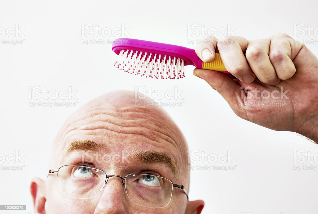 Bald man attempts to brush his non-existent hair stock photo