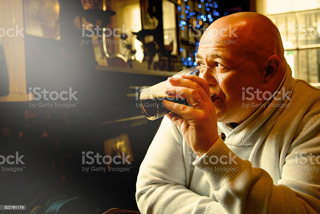 bald man drink pint of stout stock photo