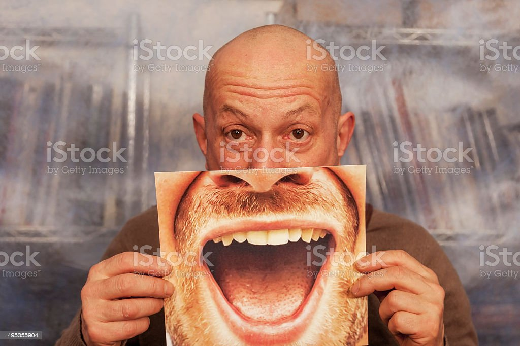 bald man holding a card with a big smile stock photo