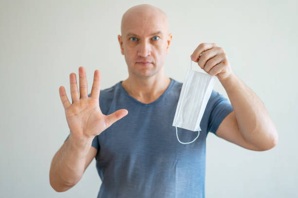 A bald man holds a medical mask in his hands, his other hand held out in protest stock photo