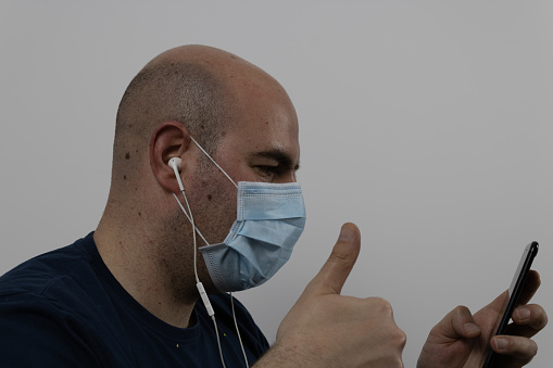 bald man in a mask making a video call with headphones