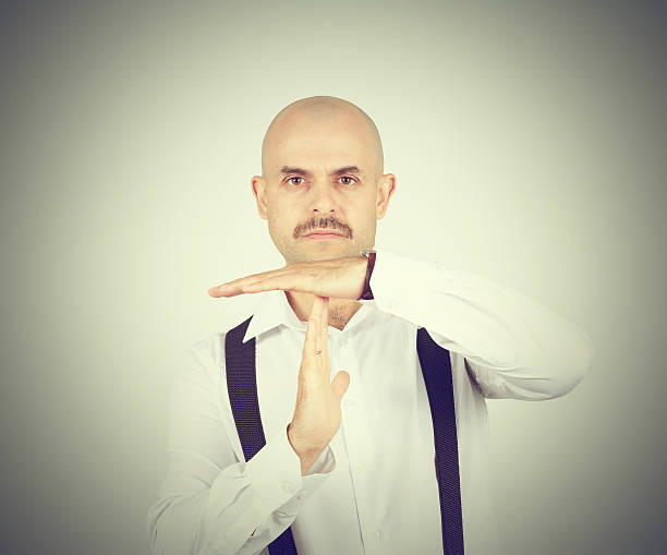 bald man showing time out hands gesture stock photo