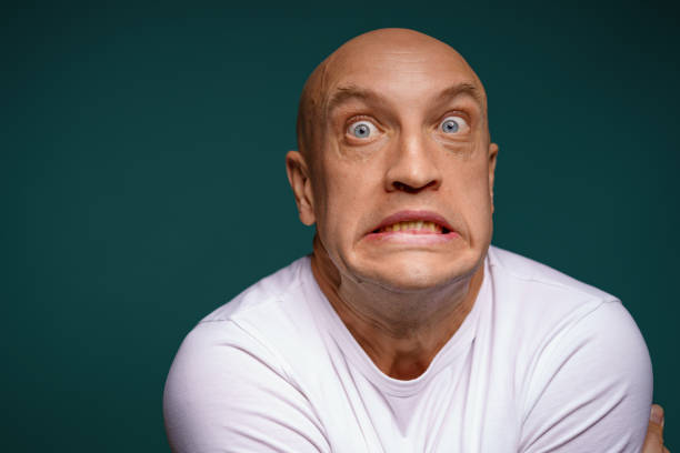 bald man with facial expressions on a blue background stock photo