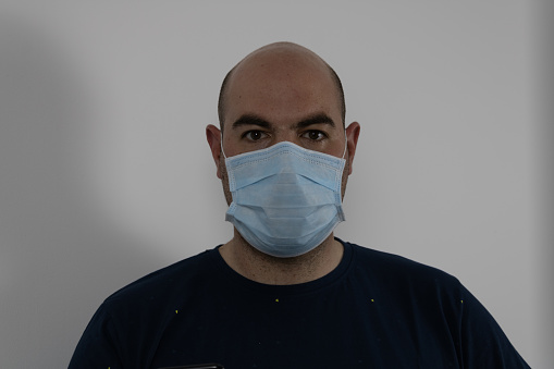 bald man with mask on white background