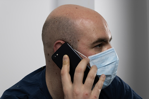 bald man with mask talking on the phone
