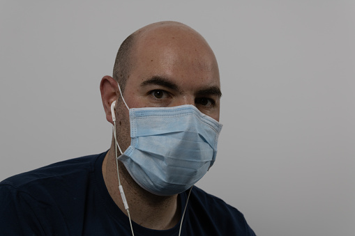 bald man with surgical mask and mobile phone earphones isolated on a white background
