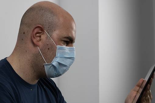 bald man with surgical mask using insulated tablet on white background