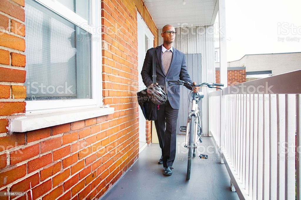 Bald mature African man leaving home with bicycle stock photo