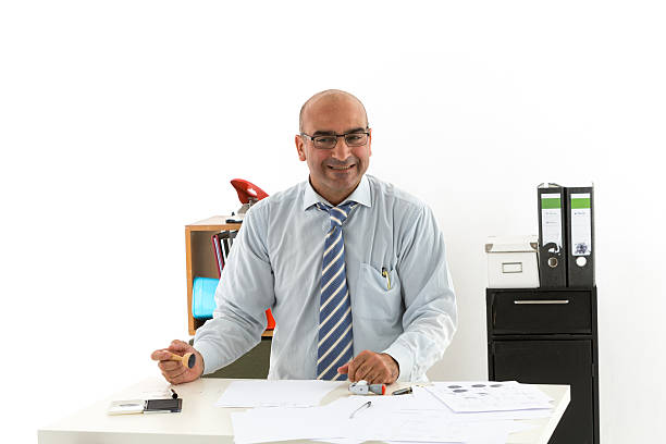 Bald office worker at desk looking laughing to the camera Bald office worker at desk looking laughing to the camera civil servant stock pictures, royalty-free photos & images