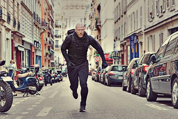 glatze weißer mann joggen in schwarz in paris straße - französisch übungen stock-fotos und bilder