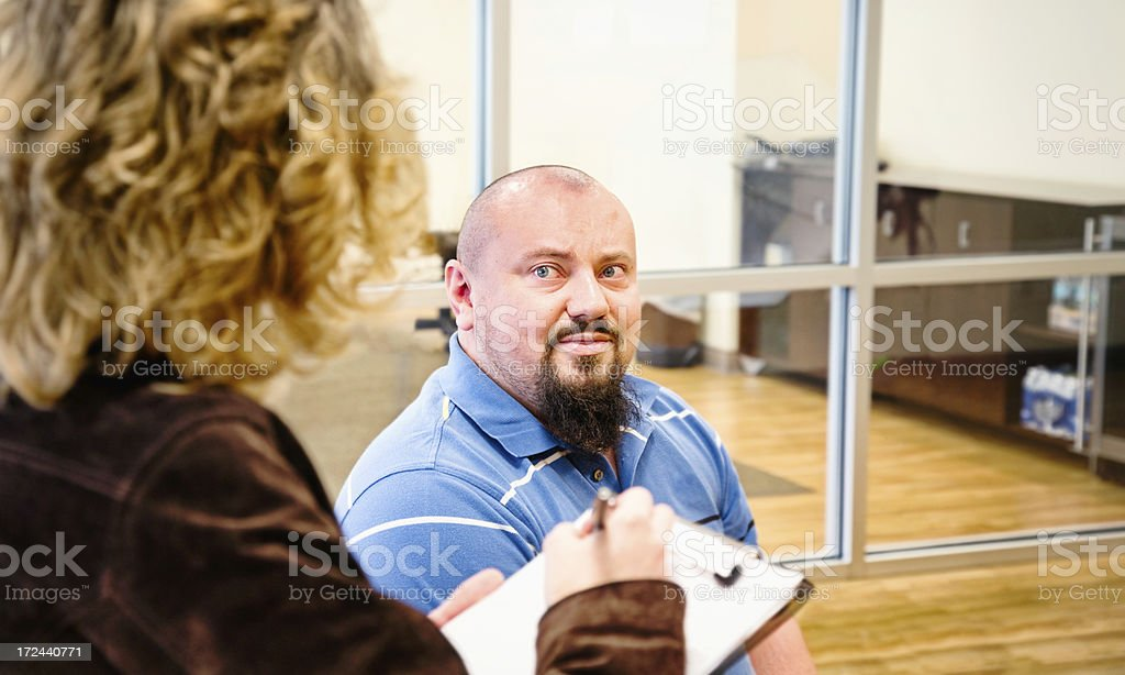 Balding man answering embarrassing questions office lobby royalty-free stock photo