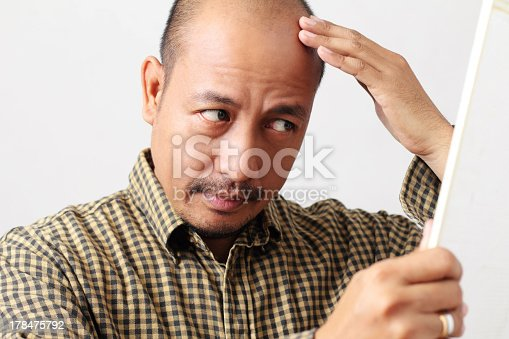 istock Balding man touching and looking at his head in the mirror 178475792