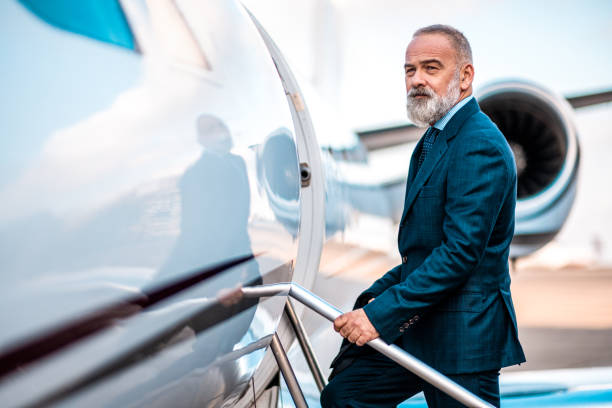 Bale business traveler wearing nice suit and beard enters private plane stock photo