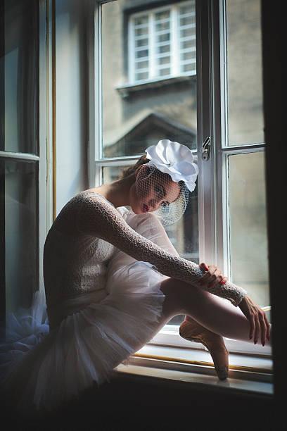 Balerina sitting in window frame ストックフォト